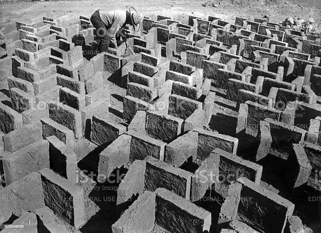 man making adobe bricks stock photo