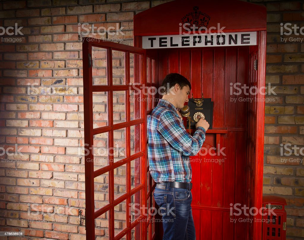 Man making call in a red telephone booth stock photo