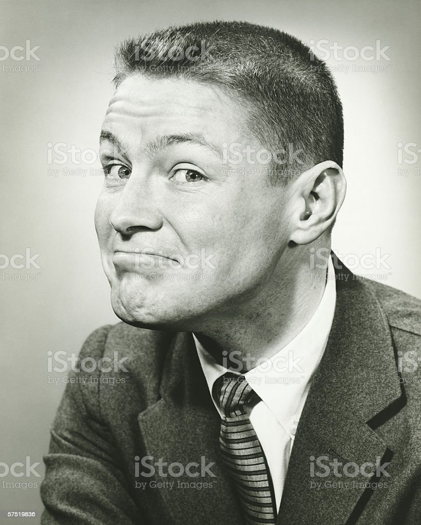 Man making face in studio, (B&W), close-up stock photo