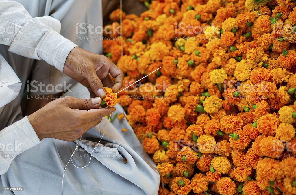 Man making flower garland royalty-free stock photo