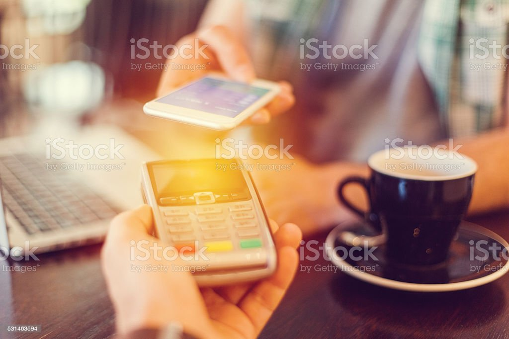Man making mobile payment in a cafe stock photo
