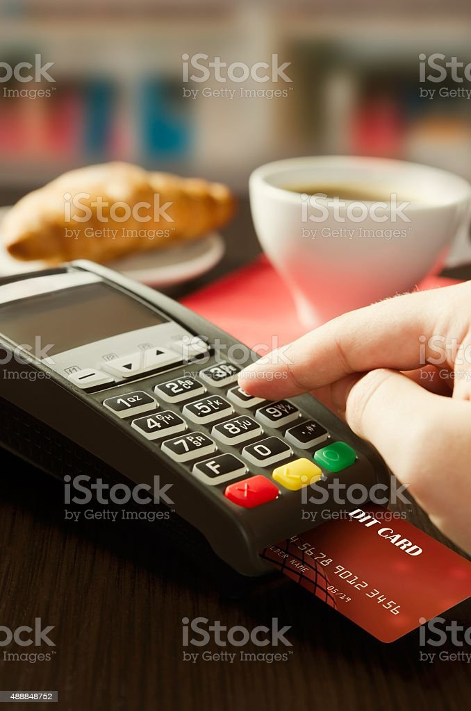 Man making payment with terminal for sale in cafeteria stock photo