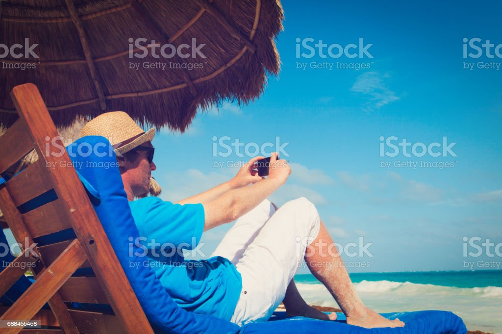 man making photo with cell phone on beach stock photo
