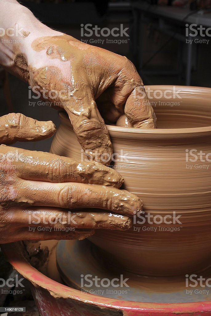 Man making pottery on spinning pottery wheel stock photo