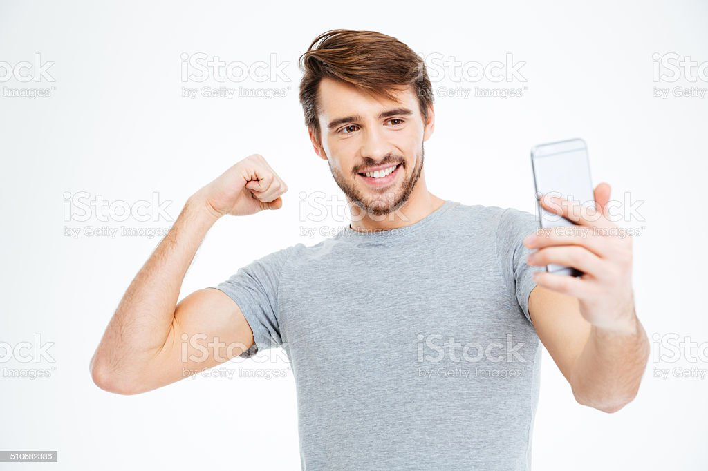 Man making selfie photo on smartphone and showing his biceps stock photo