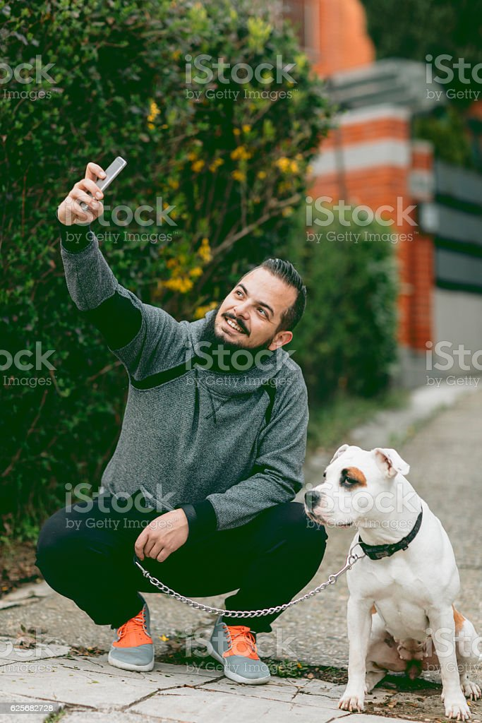 Man Making Selfie With His Dog Outdoors. stock photo