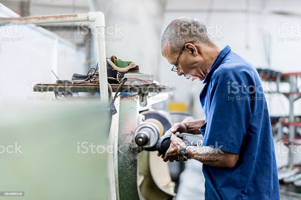 Man making shoes at a factory stock photo