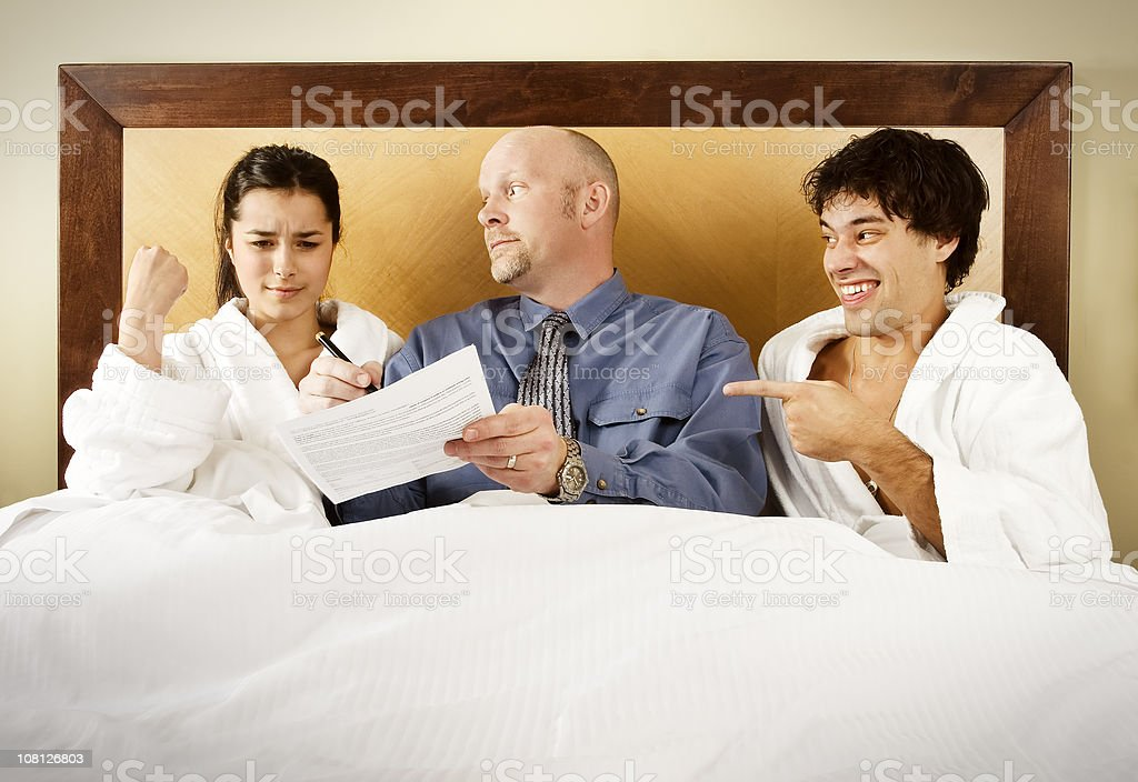 Man Making Woman Sign Legal Papers in Bed stock photo