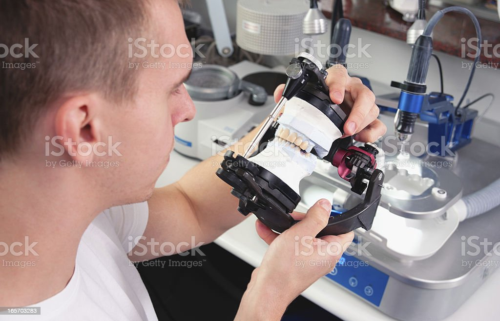 A man manufacturing ceramic crowns stock photo