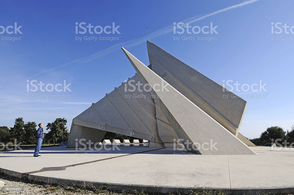 man marvelling at huge sundial, France stock photo