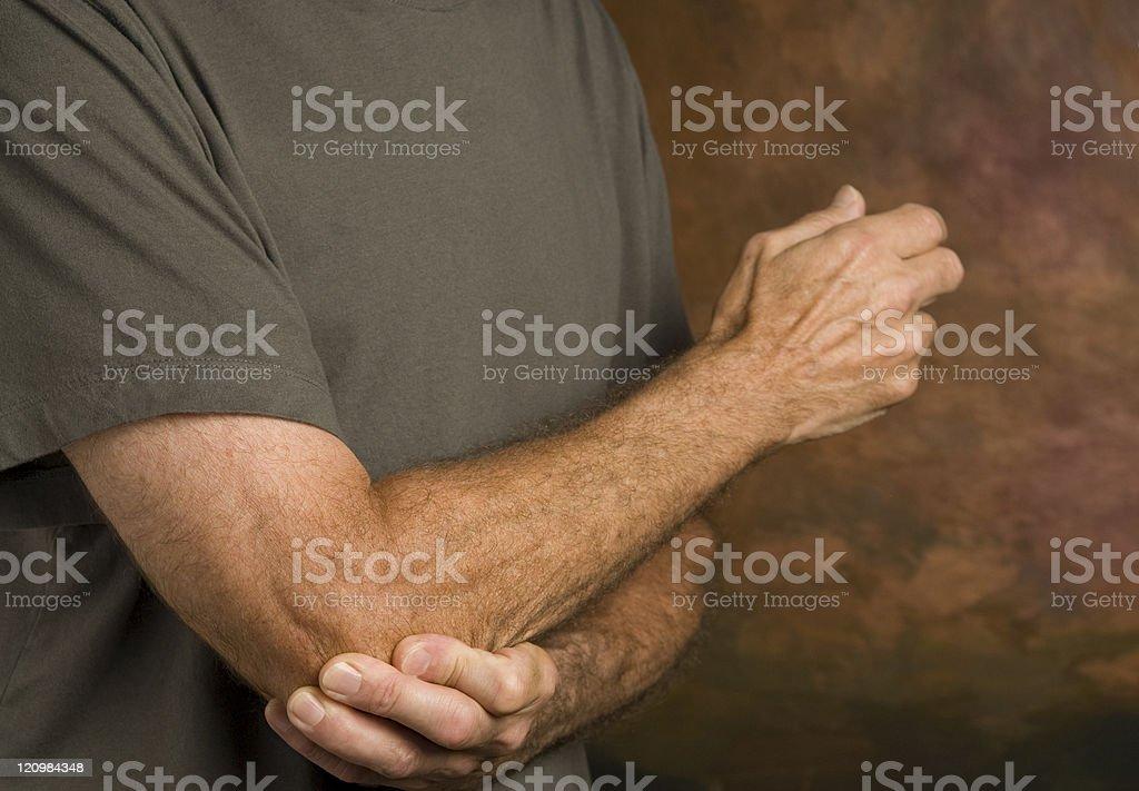 man massaging elbow in pain stock photo