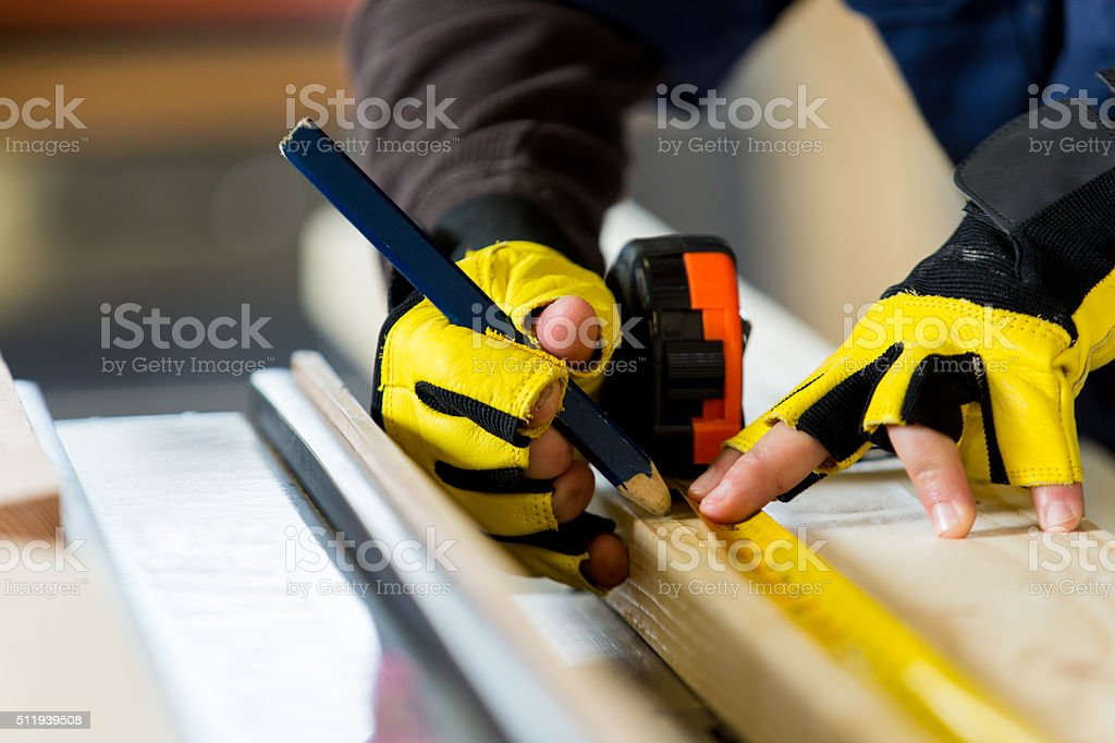 Man measures board in woodworking workshop stock photo