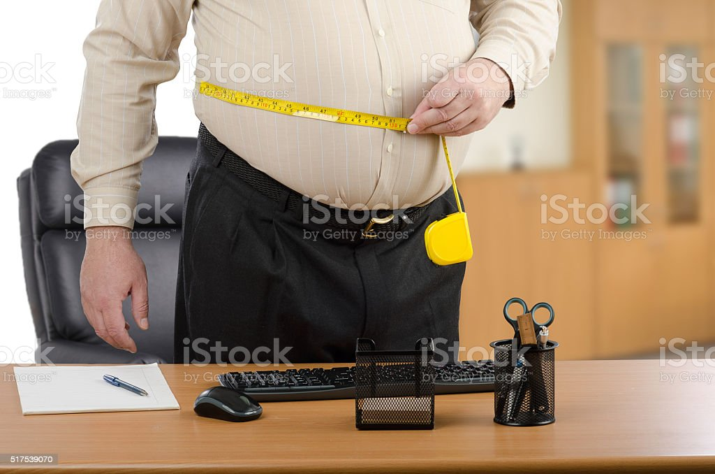 Man measures his waist by tape meter at the desk stock photo