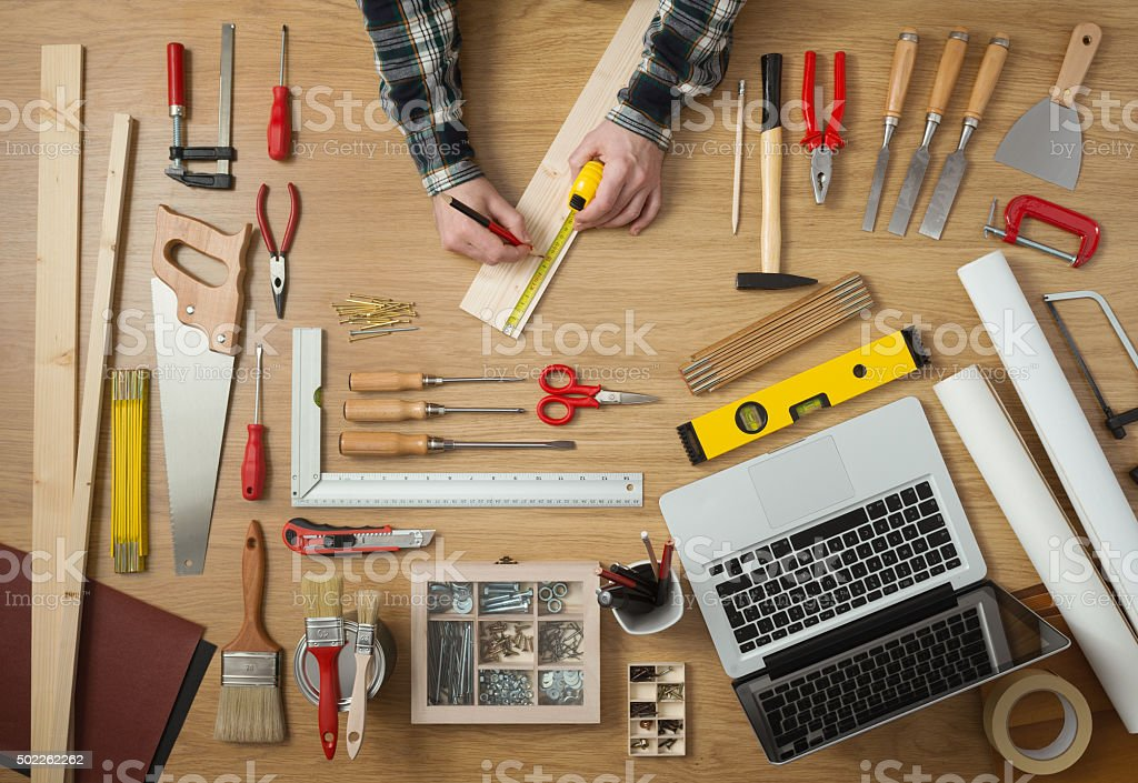 Man measuring a wooden plank stock photo
