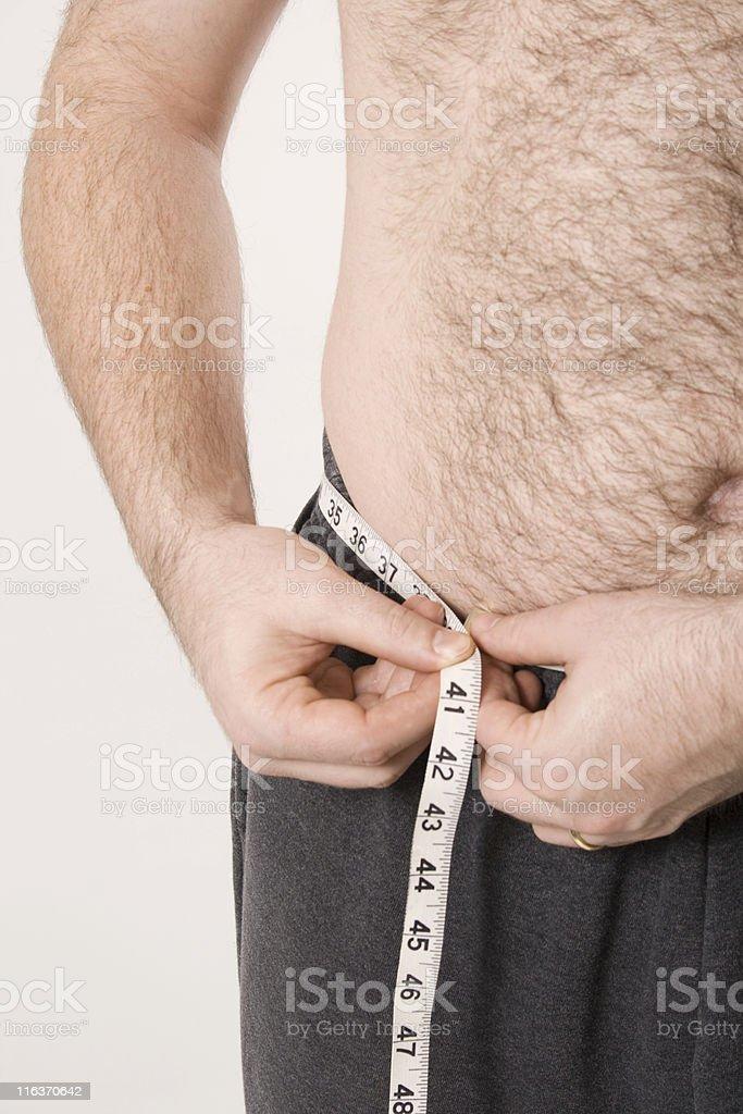 Man measuring his waist royalty-free stock photo