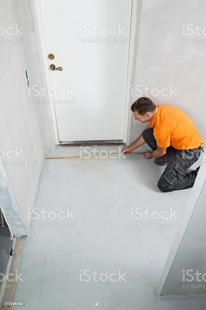 Man measuring on floor stock photo