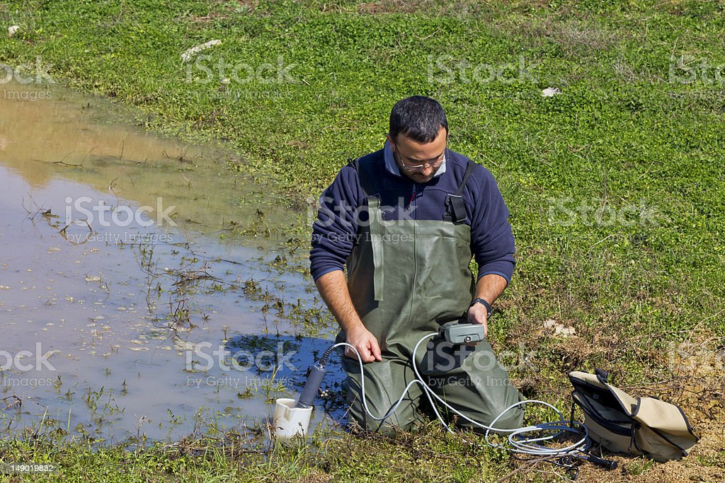 A man measuring the water quality stock photo