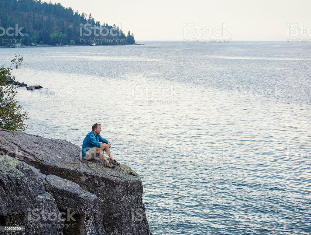 Man meditating and praying on cliff edge overlooking ocean stock photo