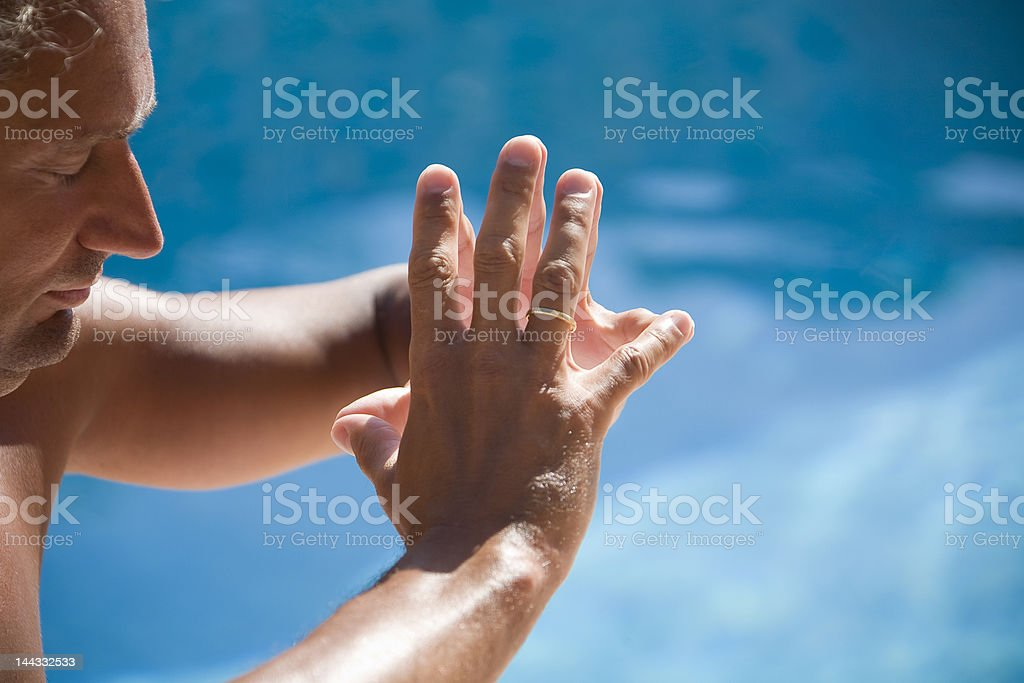 man meditating at the swimming pool side royalty-free stock photo
