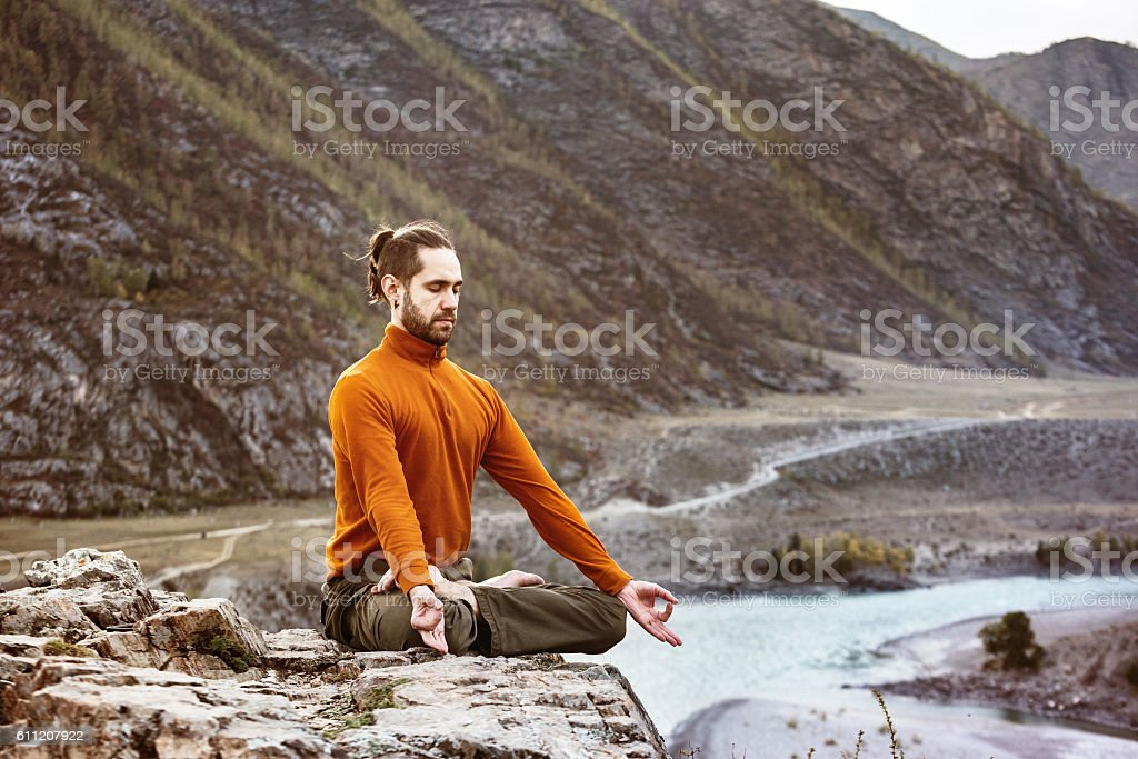 Man meditating in the mountains stock photo