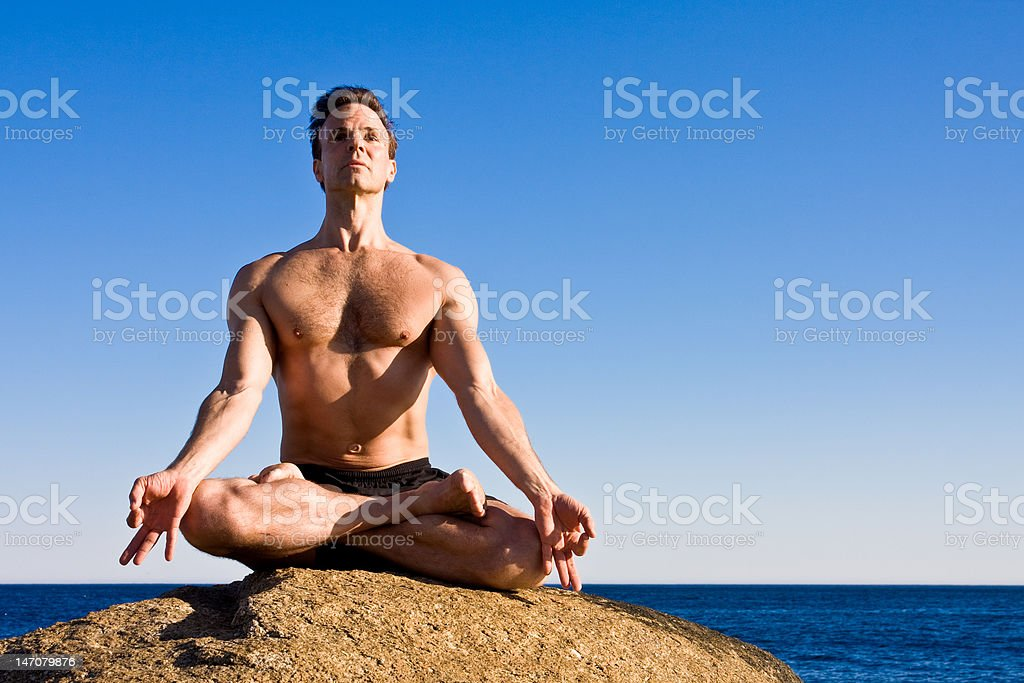 man meditating on a boulder royalty-free stock photo