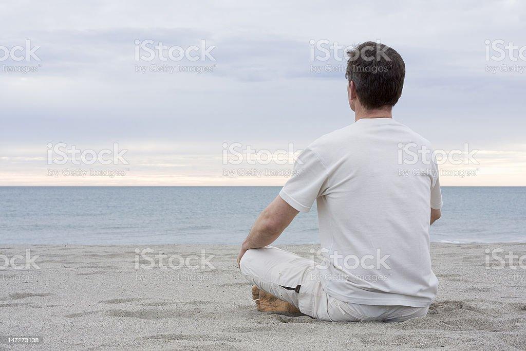 Man meditating on beach stock photo