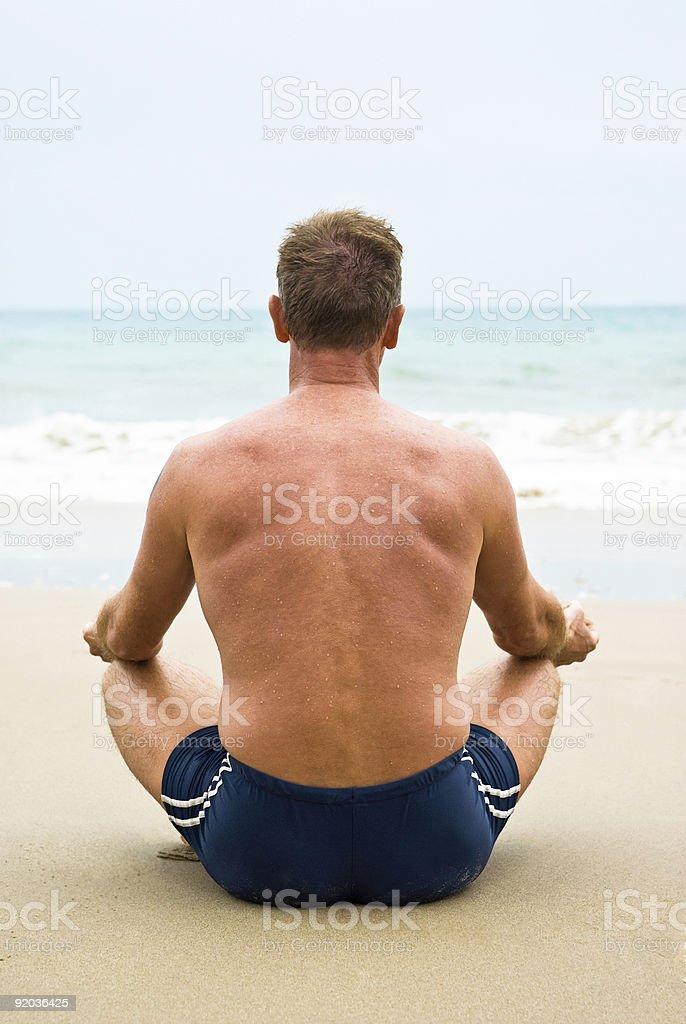 man meditating on beach. stock photo