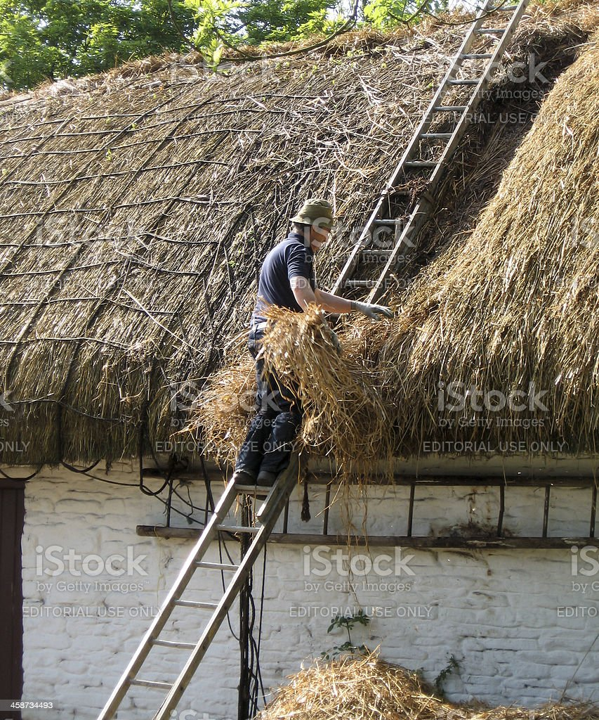 Man mending thatch stock photo