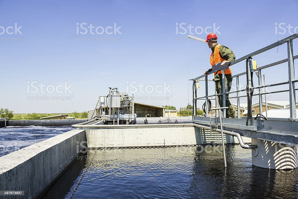 Man monitor filtering water in factory. stock photo