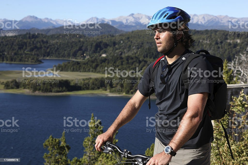 Man Mountain Biker with Mountains and Lake in Background royalty-free stock photo
