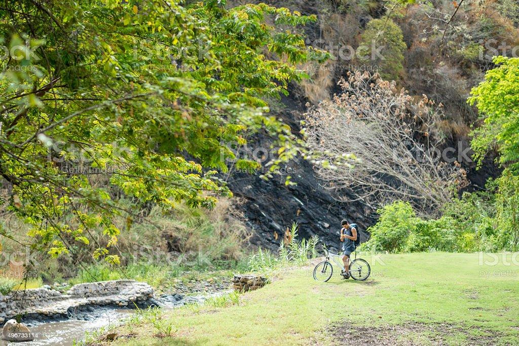 Man mountain biking texting on his cell phone stock photo