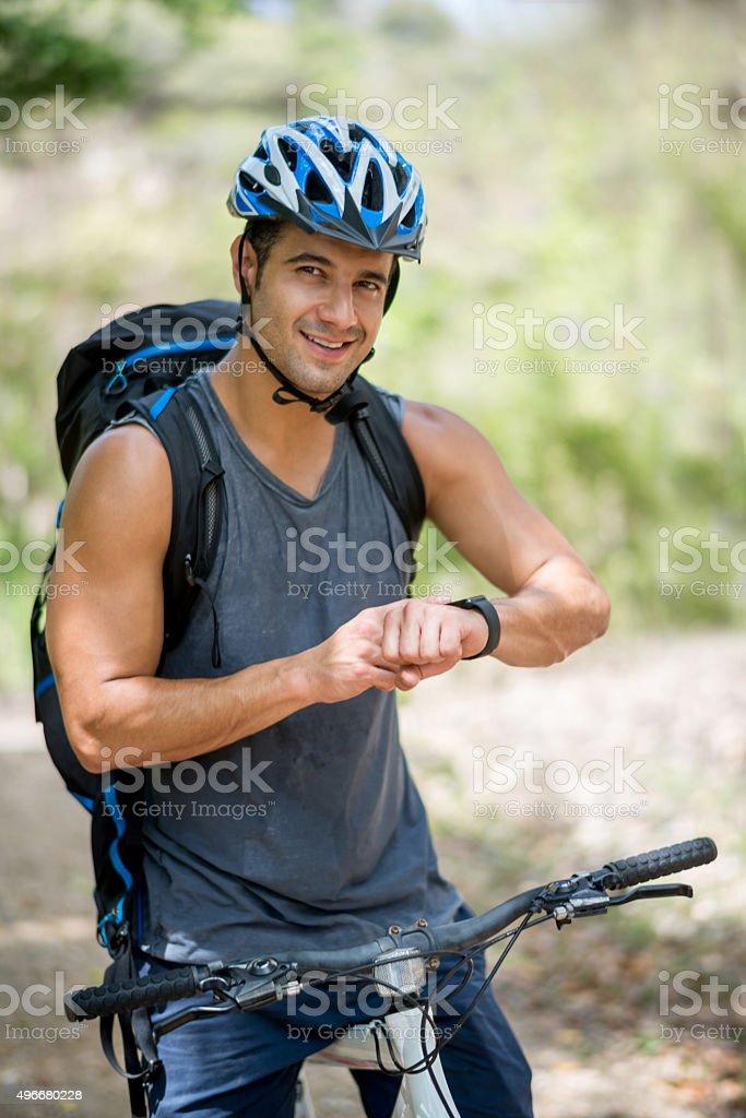 Man mountain biking using a smart watch stock photo