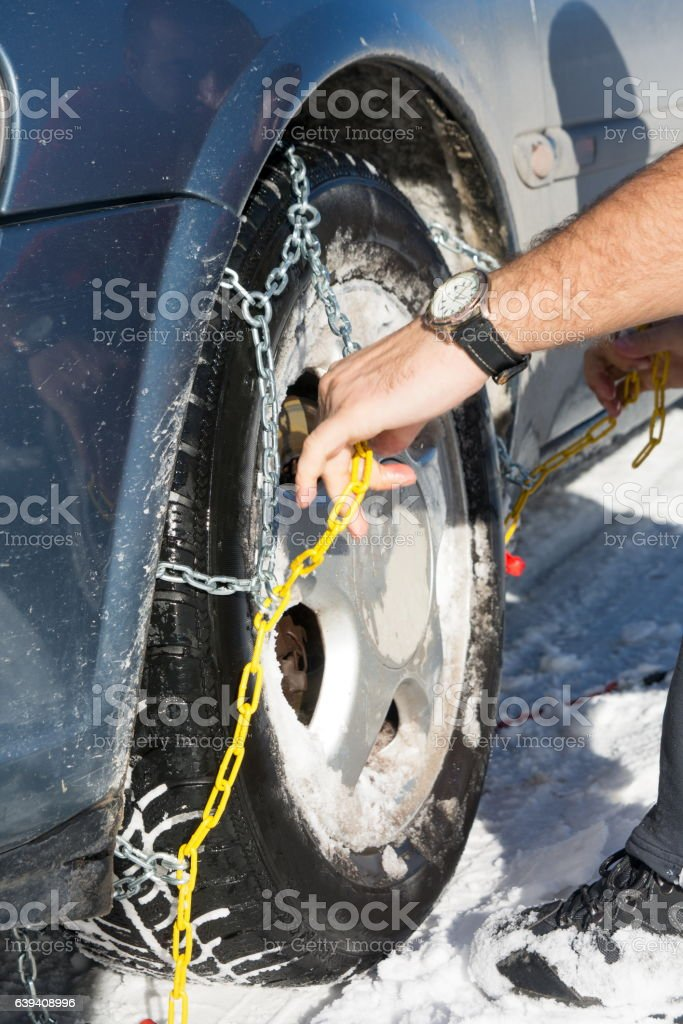 Man mounting snow chains on wheels stock photo