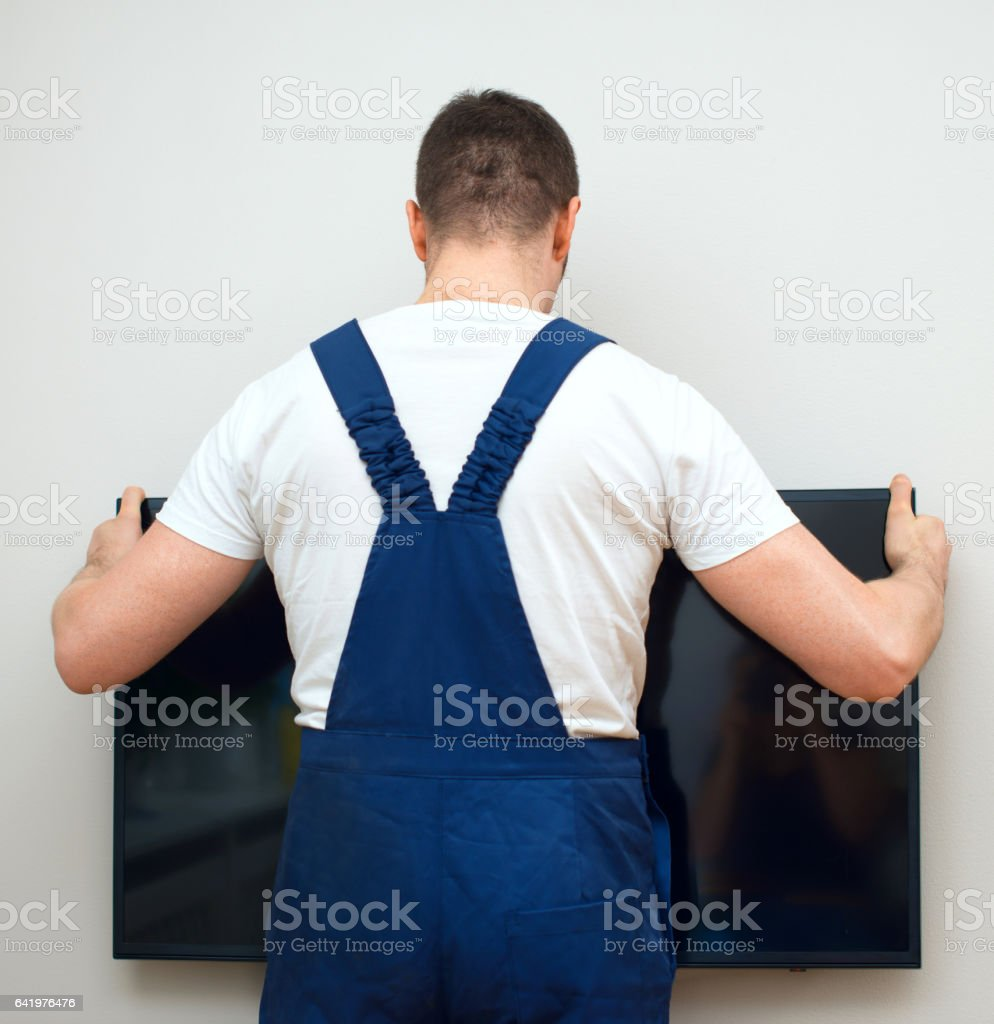 Man mounting TV on the wall. stock photo