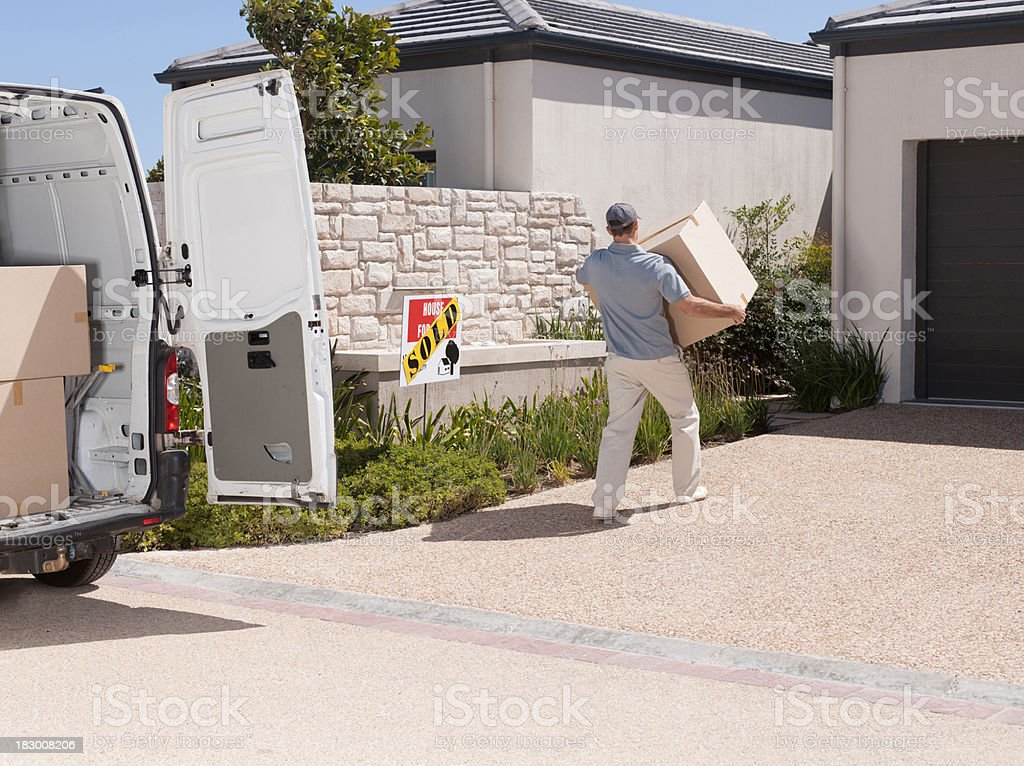 Man moving large box into new home stock photo