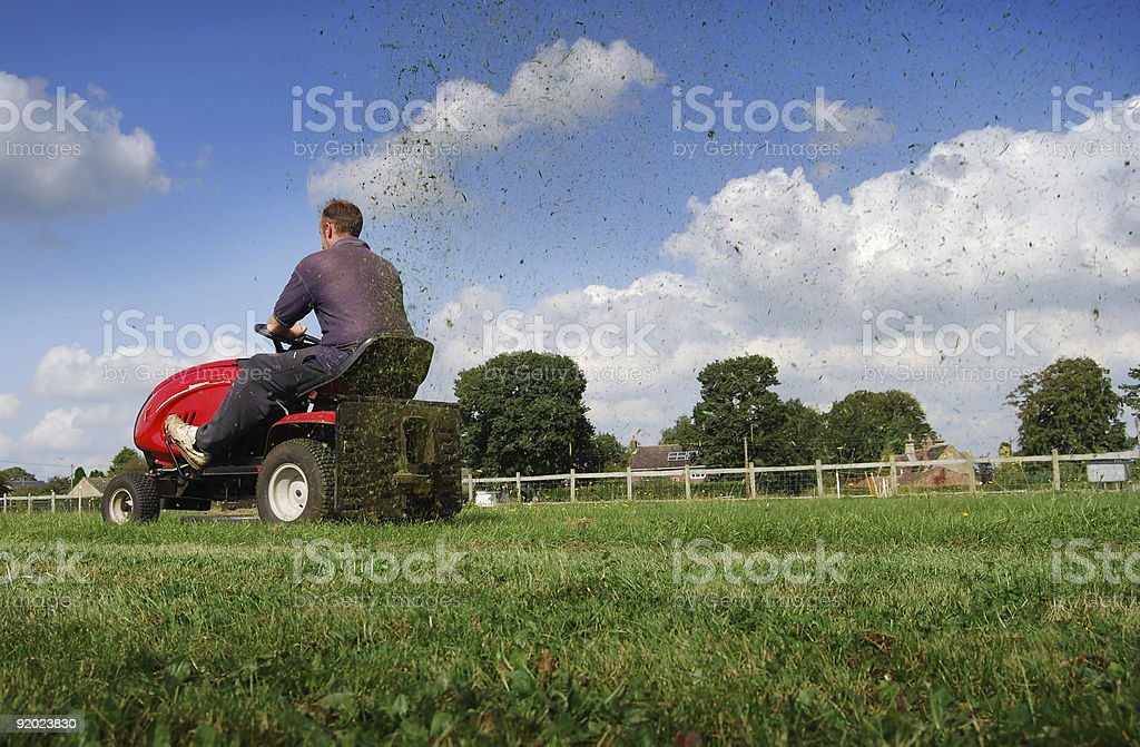 Man mowing the grass on a riding mower stock photo