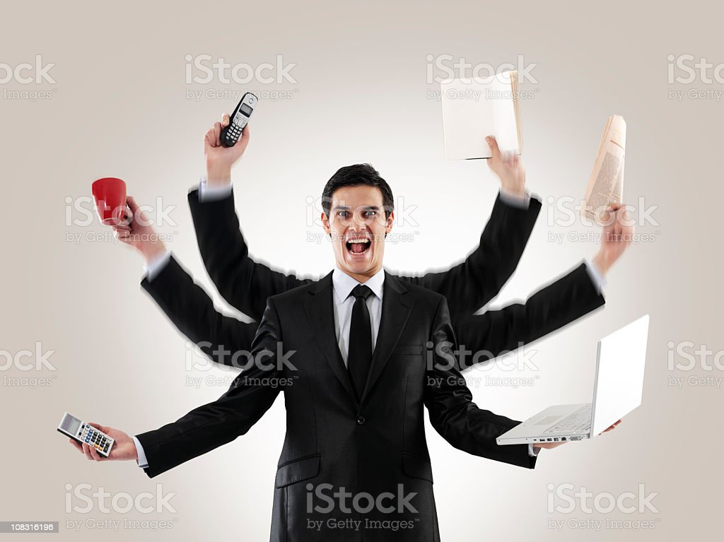A man multitasking with several arms holding items stock photo