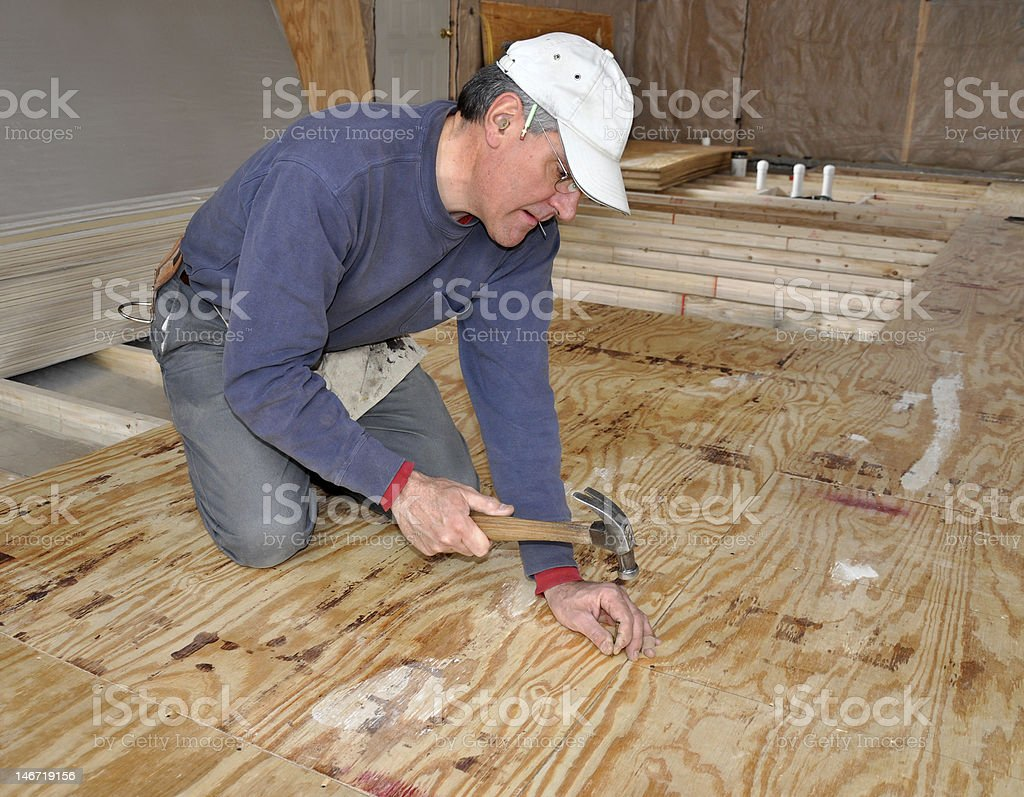 Man nailing down plywood sub-floor stock photo