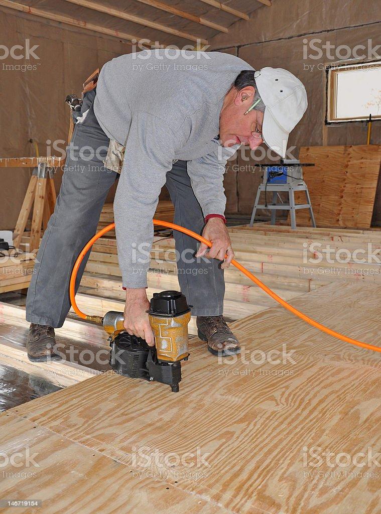 Man nailing plywood floor with nail gun stock photo