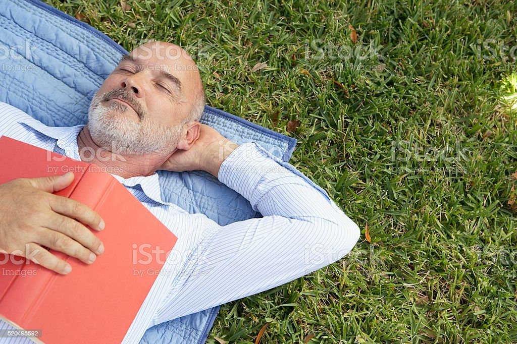 Man napping with a book on his chest stock photo