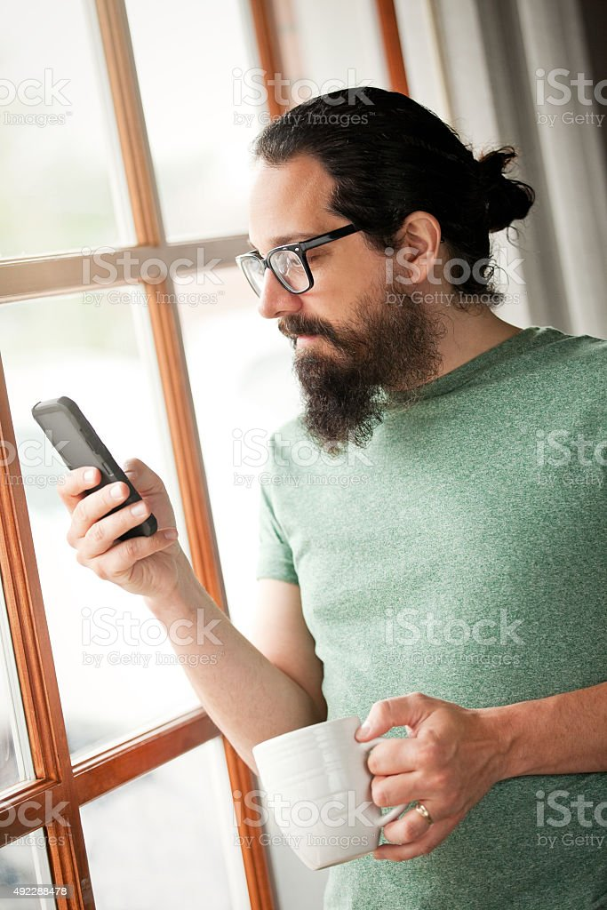 Man Near Large Window Checking Phone stock photo