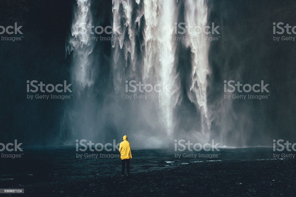 Man near the waterfall stock photo