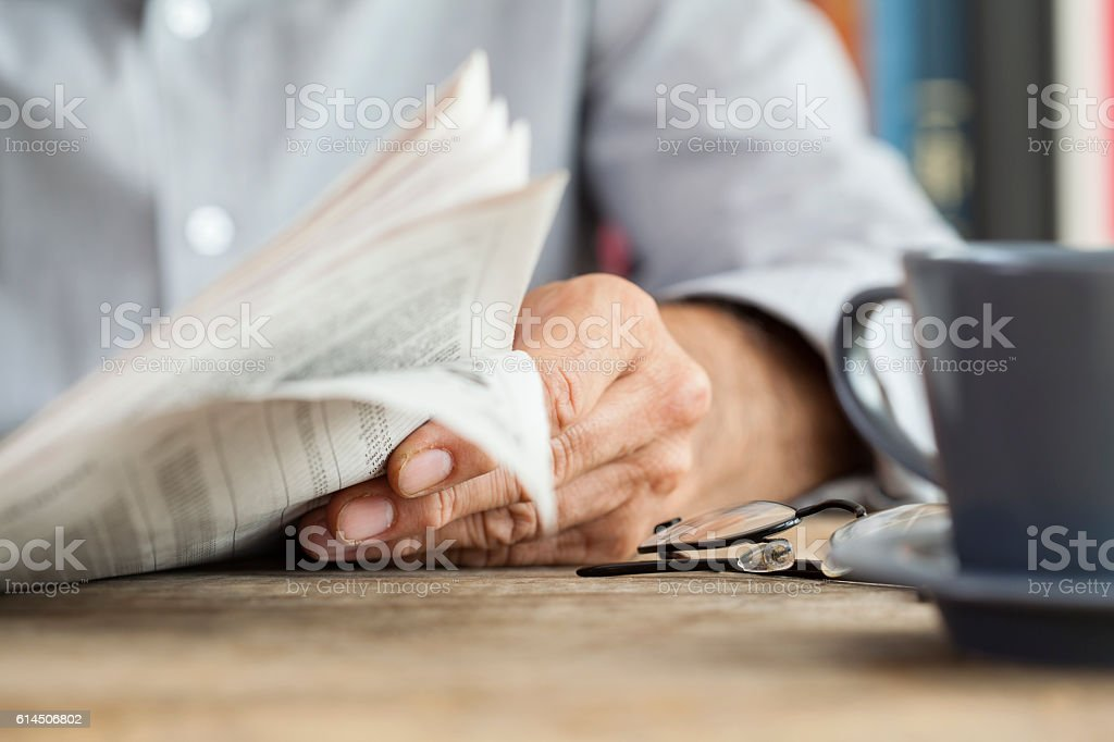 Man newspaper reading on table stock photo