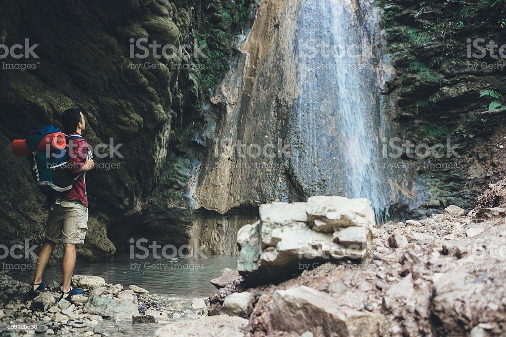 Man next to a waterfall after mountain trekking stock photo