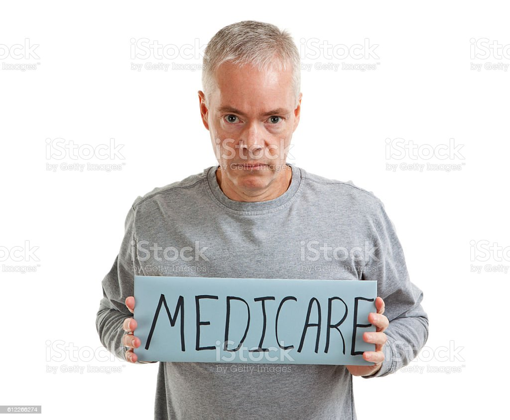 Unhappy man holding a sign saying Medicare, isolated on a white...