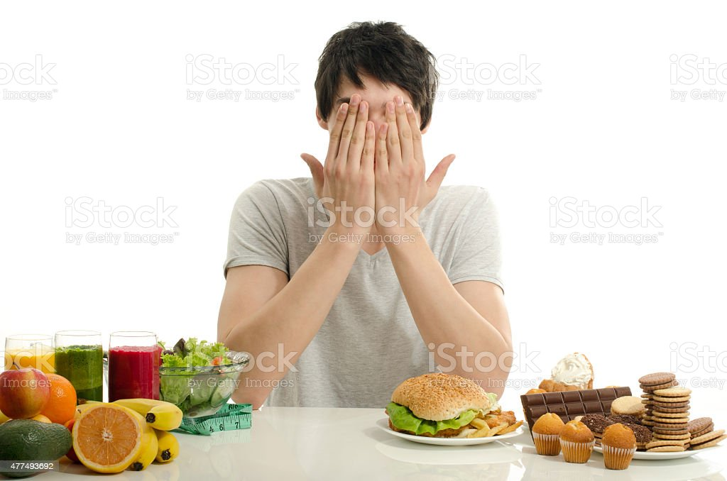 Man not wanting to choose between healthy food and junk-food. stock photo