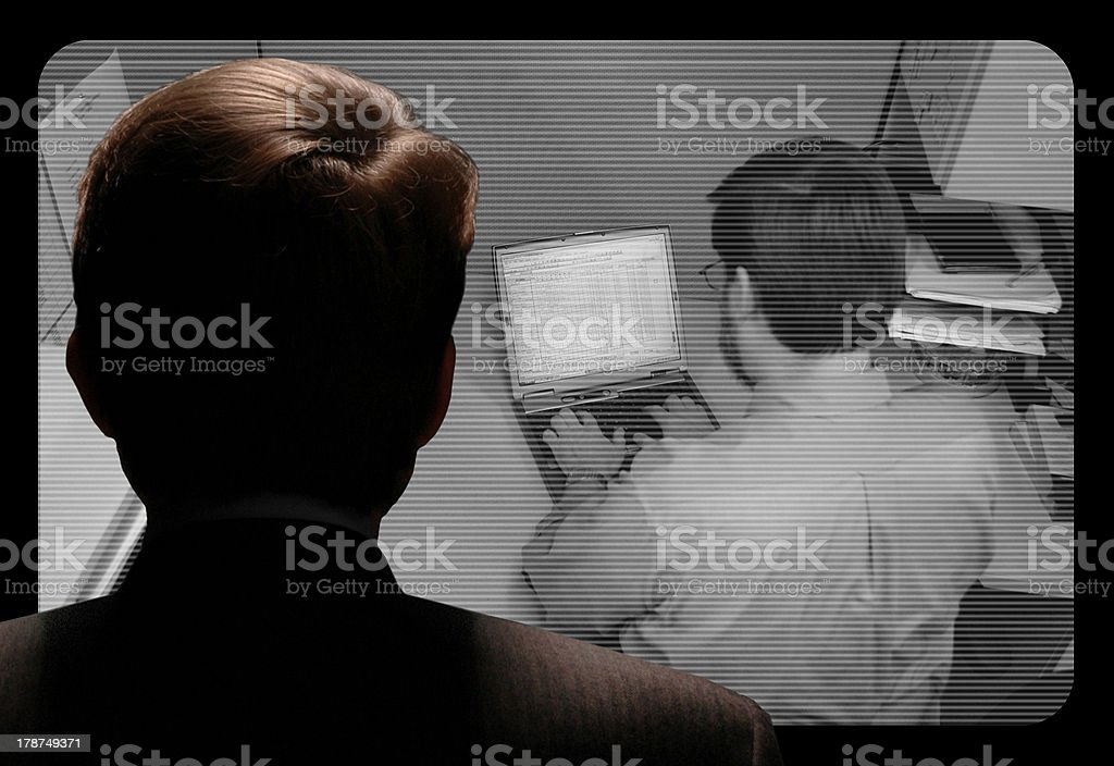 Man observing an employee work via video camera stock photo