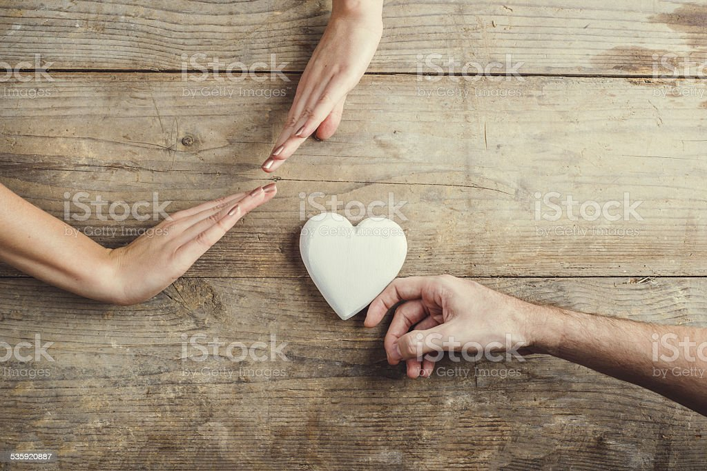 Man offering a heart to a woman. stock photo