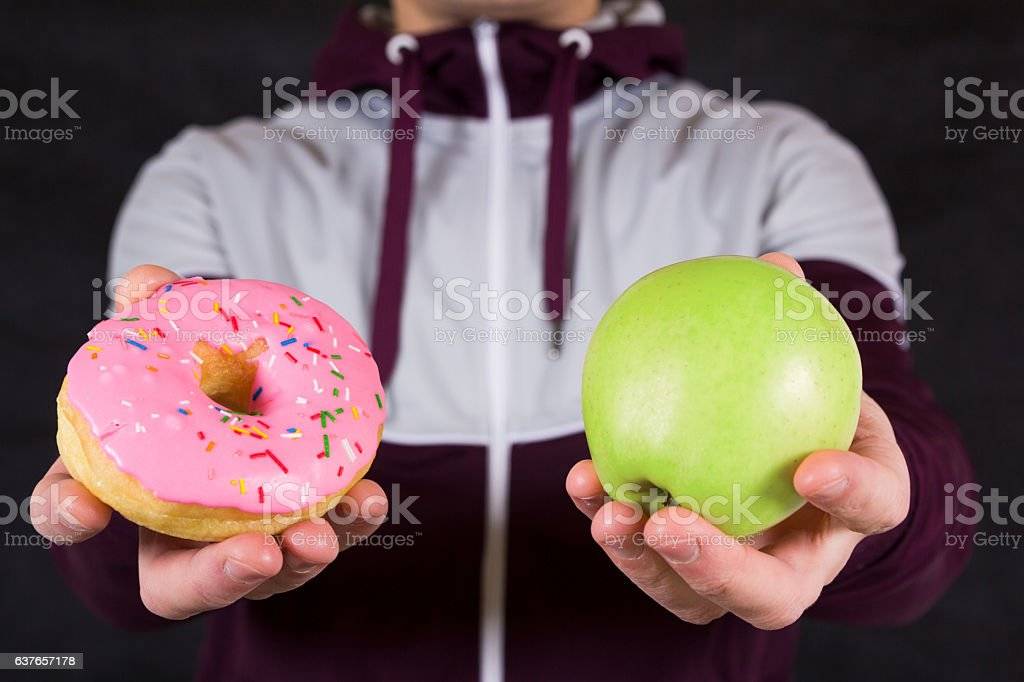 Man offering apple and donut as concept of healty lifestyle stock photo