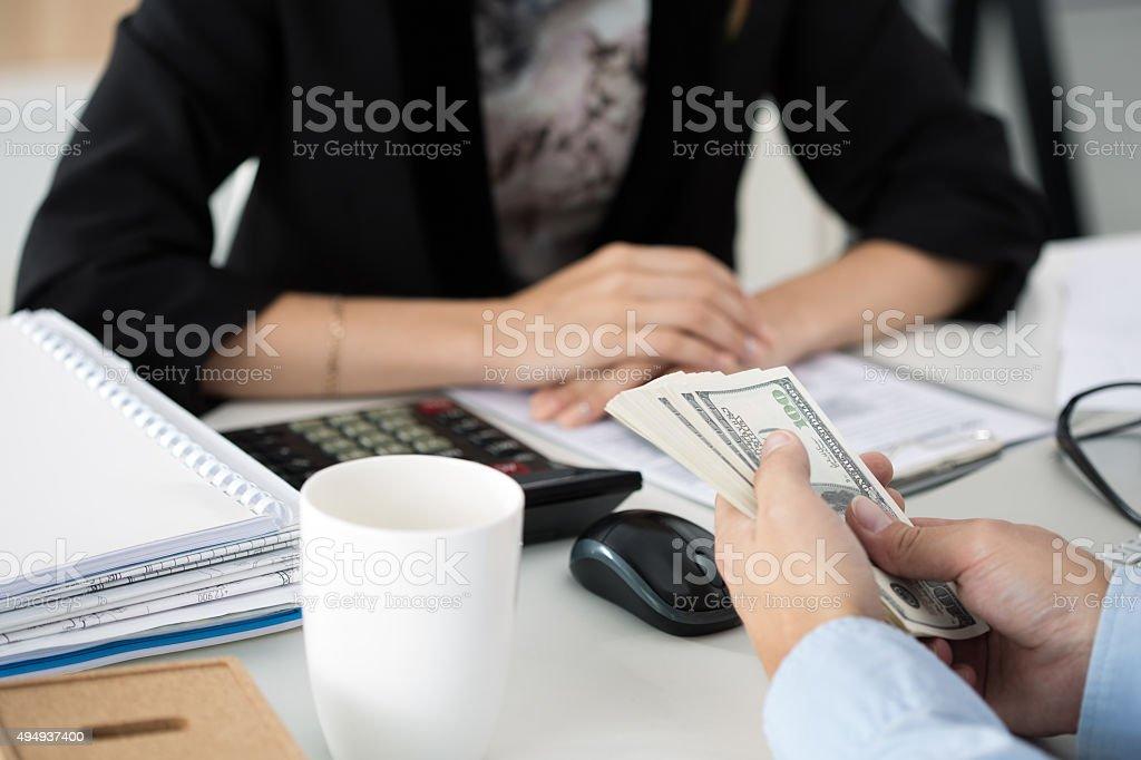 Man offering batch of hundred dollar bills stock photo